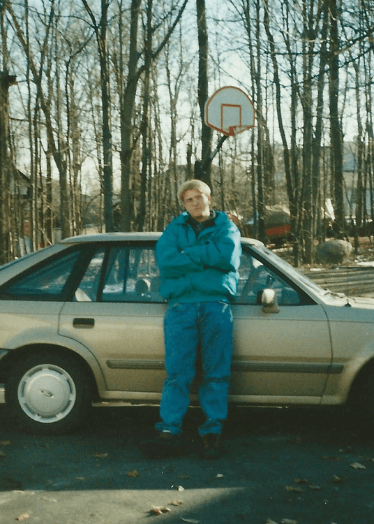 Jason-Sirotin-Poses-in-a-charlotte-hornets-jacket-next-to-an-89-ford-escort