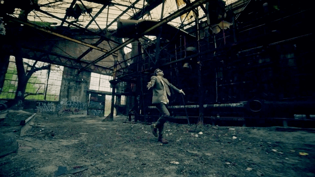 16 OS - 3's Company music video still of a man in a warehouse.