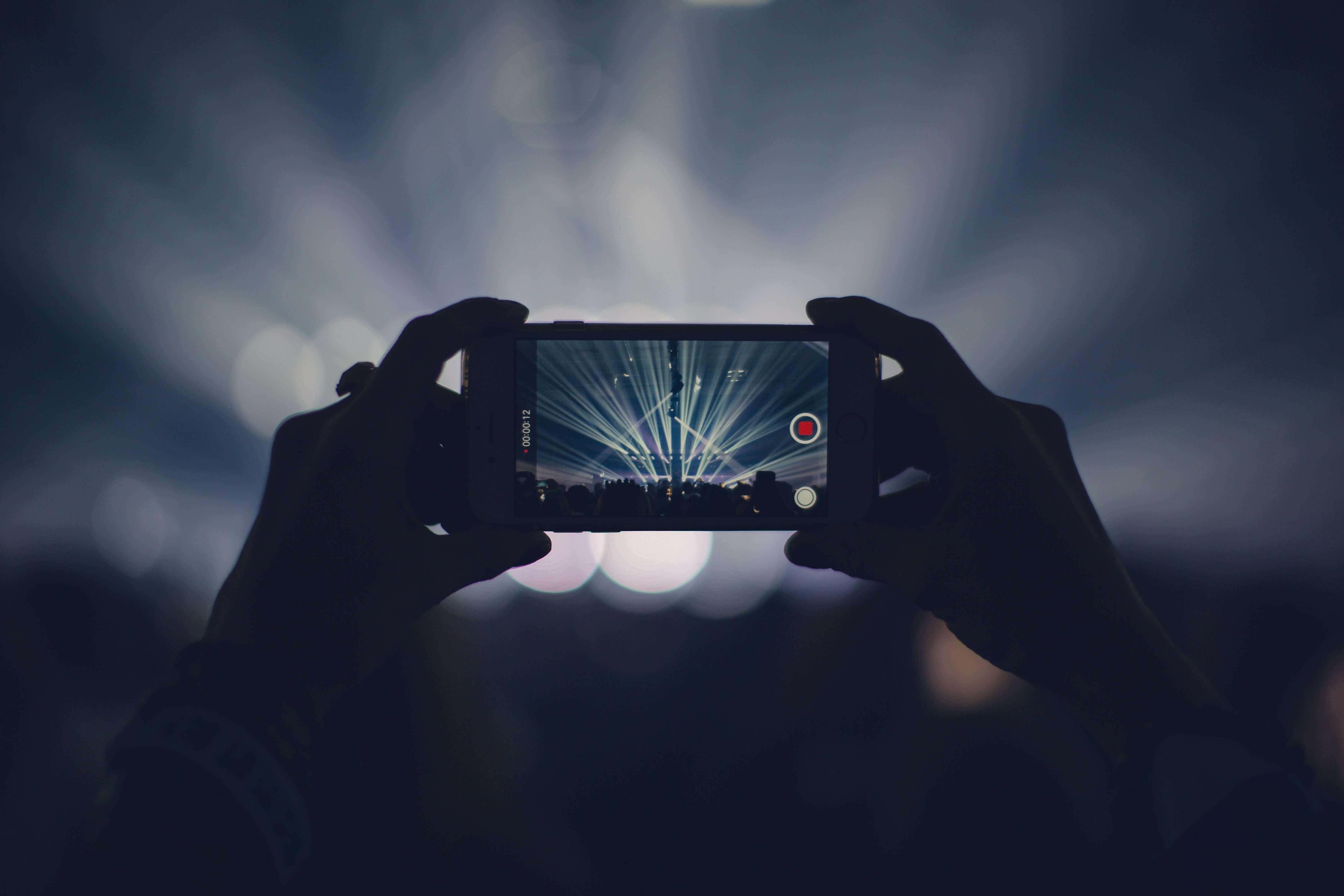 Branded content creator recording concert with smartphone.