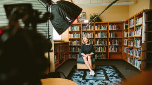 A woman sits during the lighting setup for a mini documentary interview.