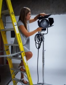 Woman wearing a dress and sandals on set (and on a ladder).