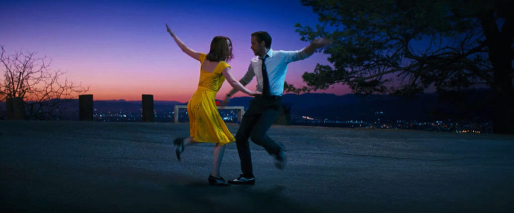 The white and yellow clothing helps Ryan Gosling and Emma Stone stand out from the background.
