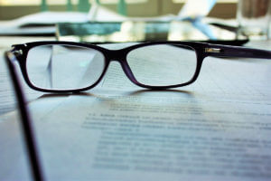 A pair of reading glasses sits on top of a contract for video production.