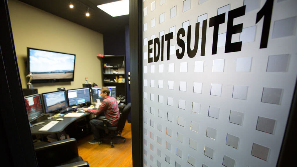 A man video edits in a post-production film editing suite while saving with Georgia tax credits and tax incentives.