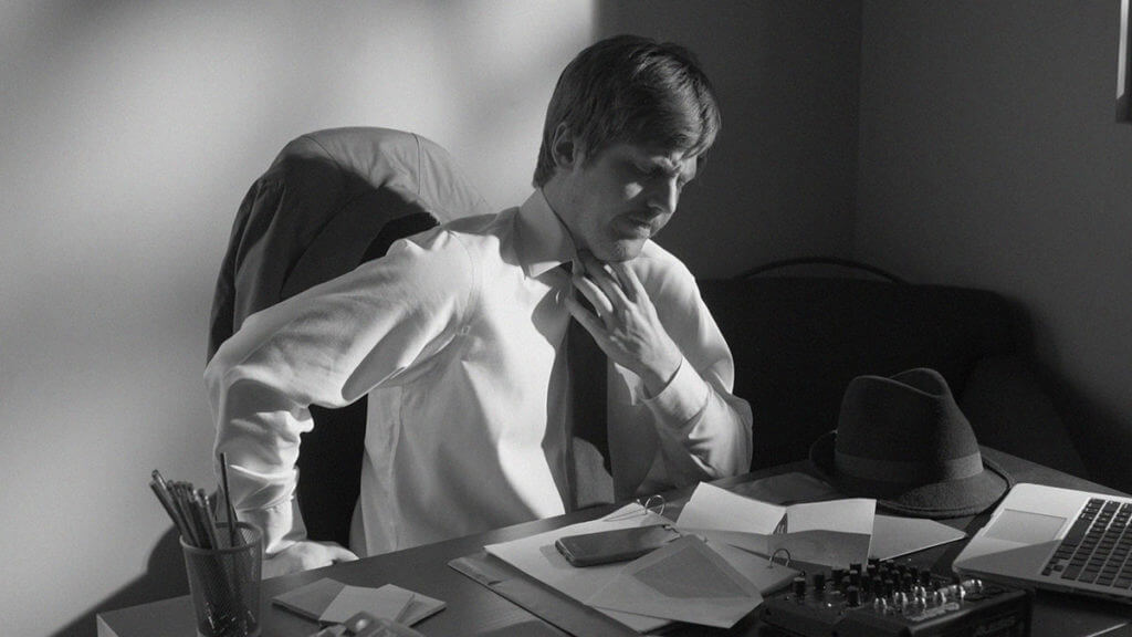 A man sits at a desk adjusting his tie in cinematic film noir style.