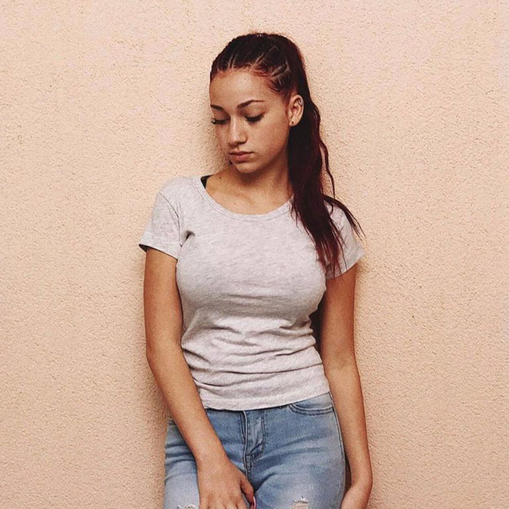 Bhad Bhabie leans against a wall looking down.