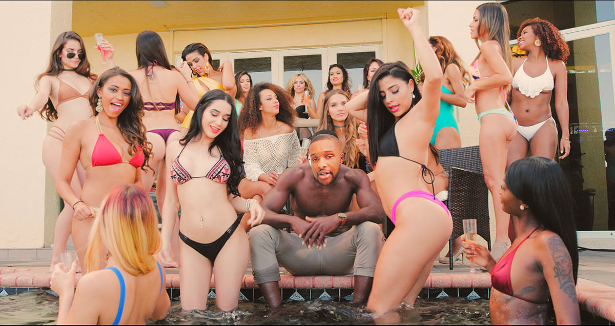 A man with a mask hides his identity while at a pool party music video surrounded by girls.