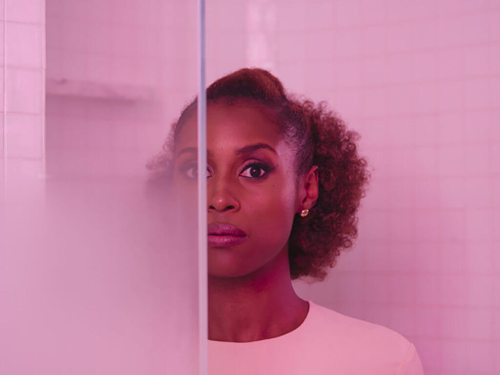 Actress Issa Rae from HBO's Insecure stands behind a glass wall with pink lighting her skin tone.
