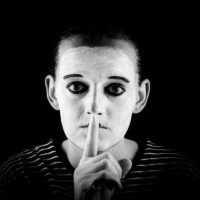 "A mime showing the ""silence please"" sign."