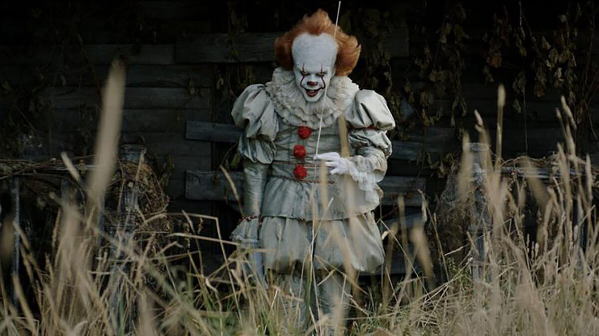 Pennywise the Clown from the horror movie It looks at us while holding a ballon by a string.