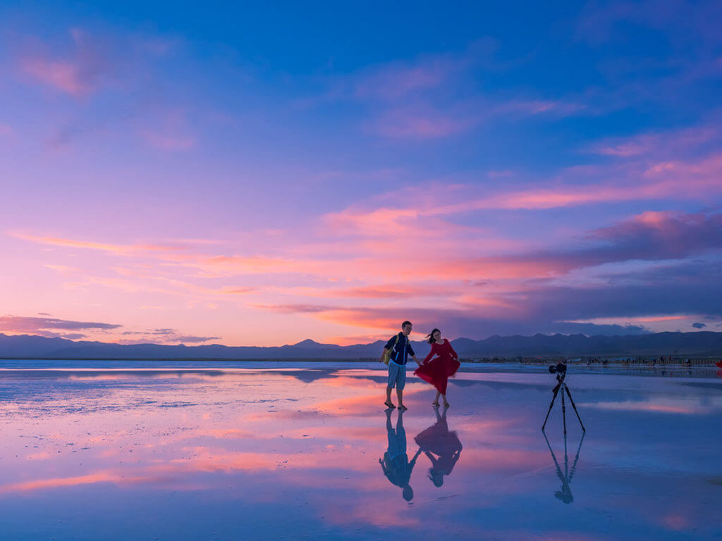 A couple stands on a frozen lake filming itself with a camera on a tripod and an beautiful pink and blue sunset in the background.