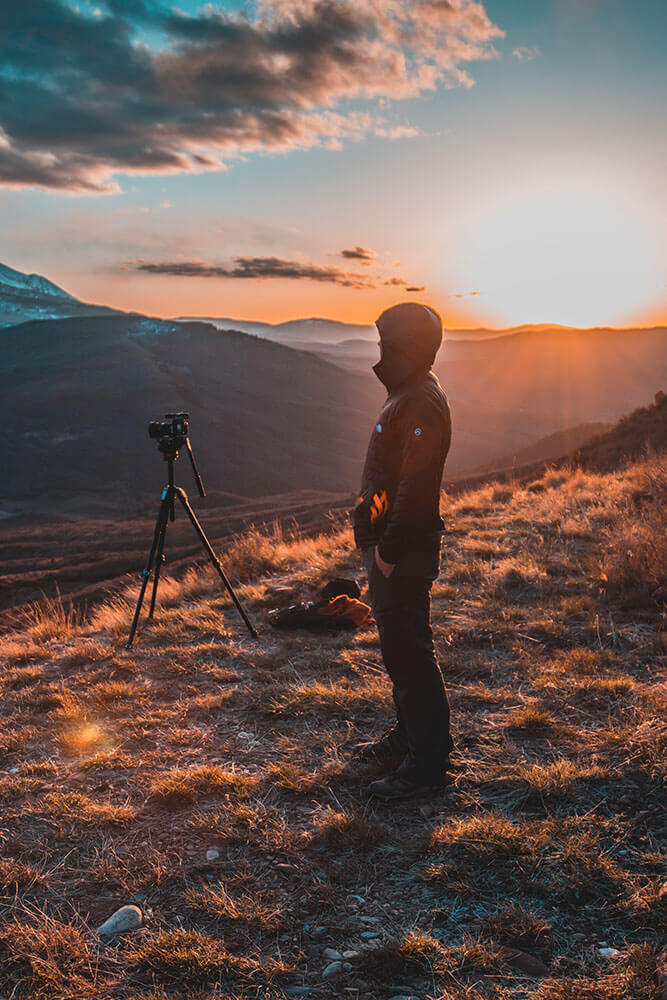 A man stands behind a camera and tripod, filming outdoor landscapes while the sun sets behind him.
