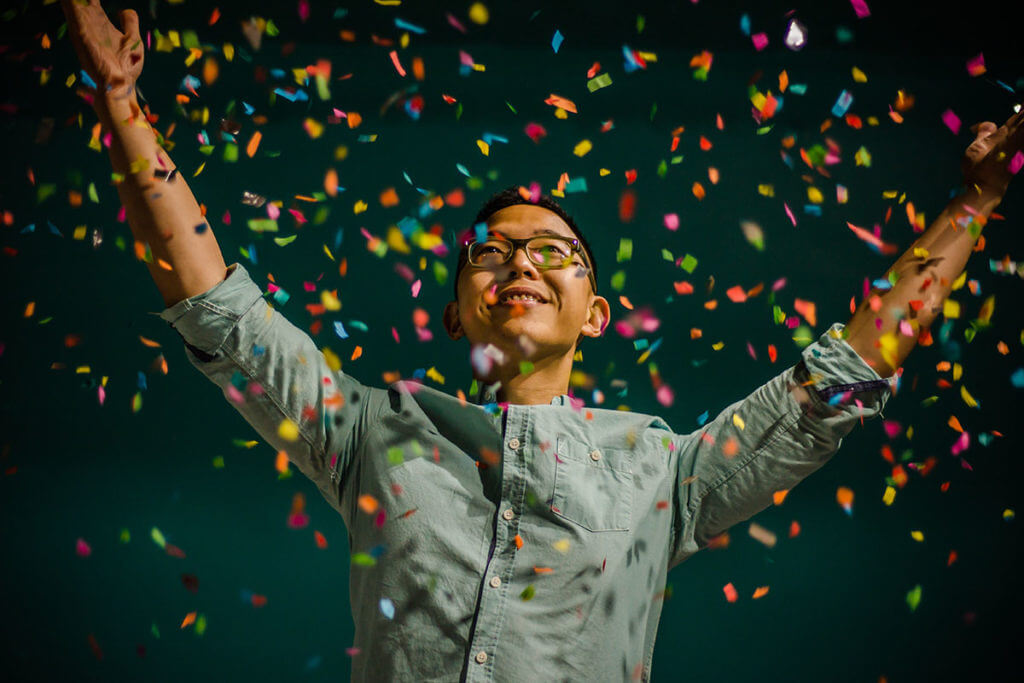 A confident man showered with confetti stands with arms raised after learning how to deal with imposter syndrome.