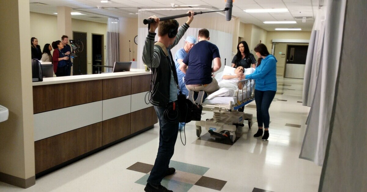 Brandon Peterson films a medical TV commercial on a gurney.