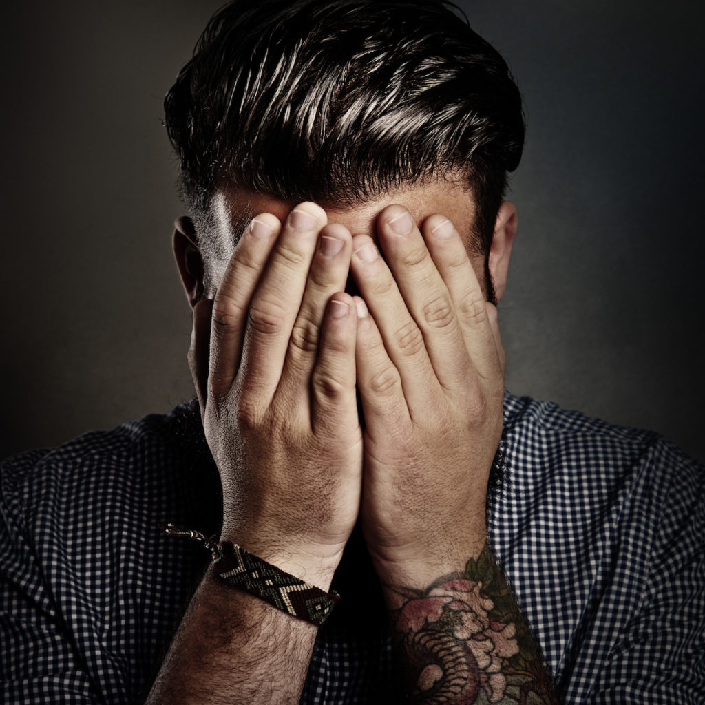 A man buries his face in his hands after a typical music video request and quote.