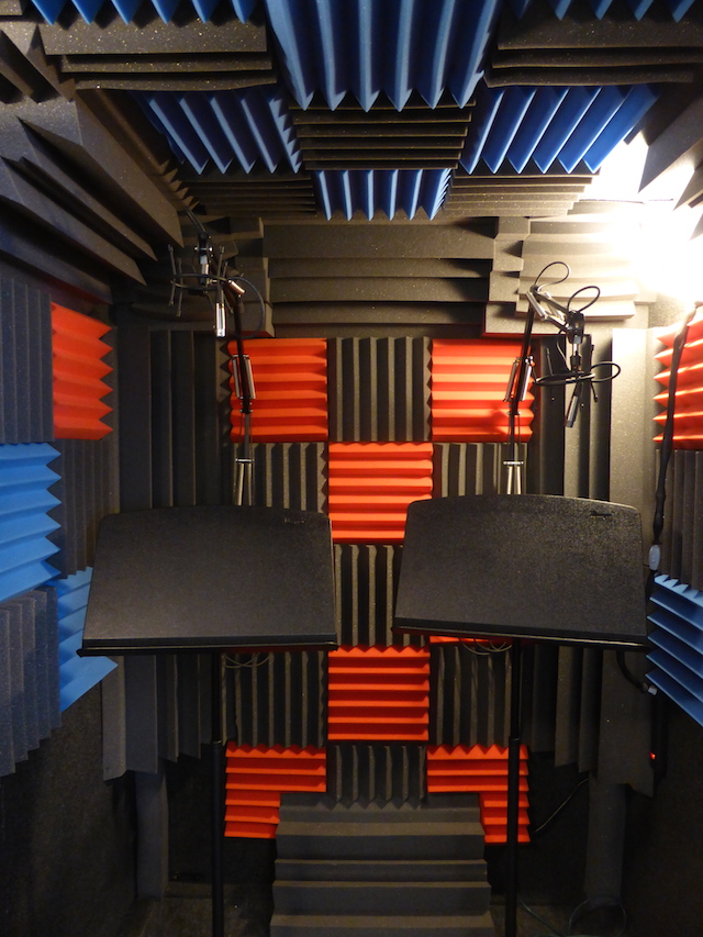A whisper room with red, blue, and charcoal acoustic padding used to record a voice-over with minimal background noise.