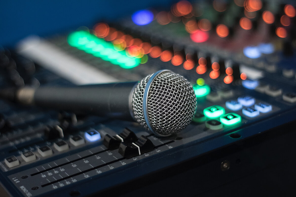 A microphone rests on top of an audio engineer sound board.