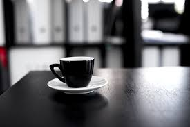 A coffee cup and saucer in focus on top of a wooden table with a blurry background.