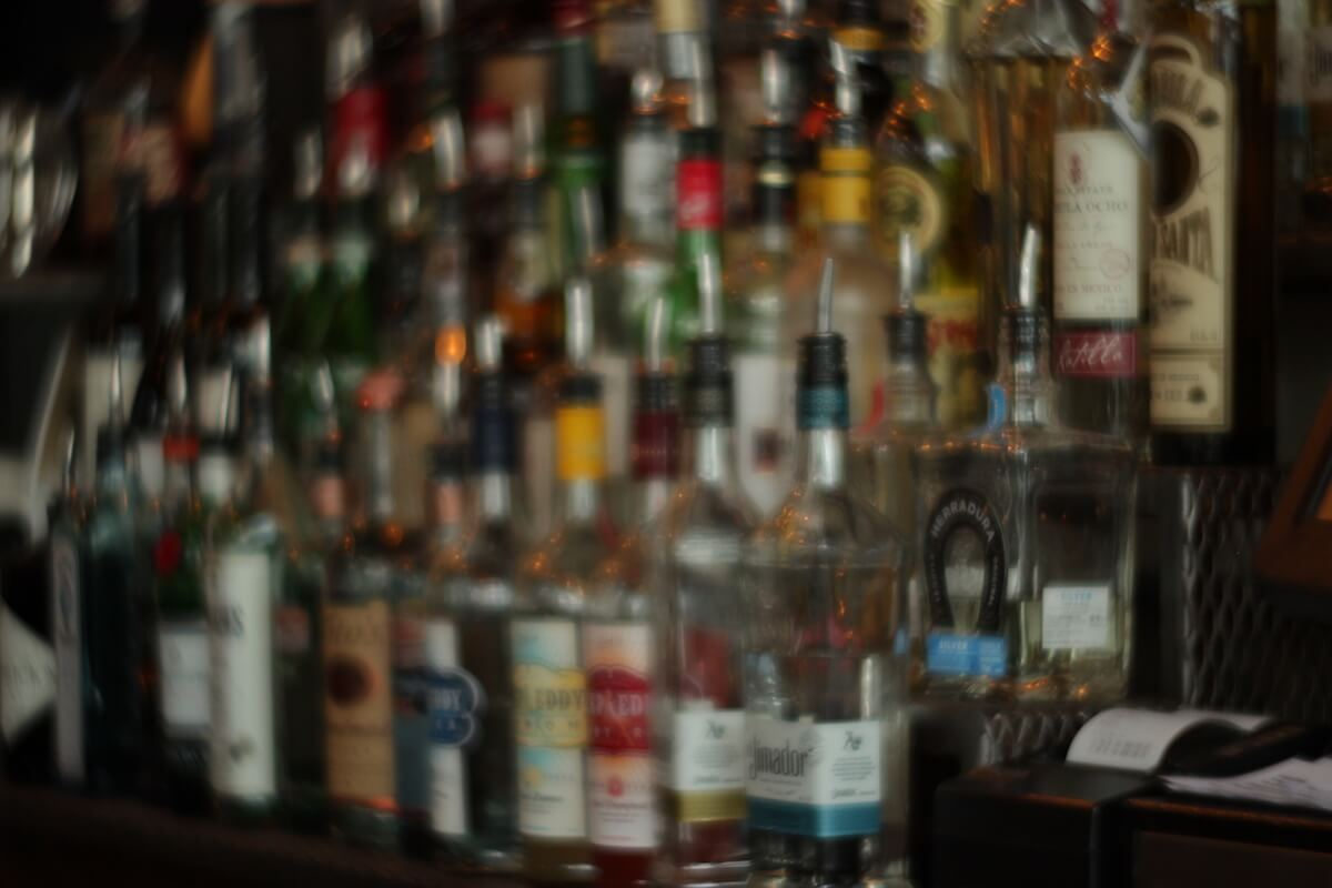 An out of focus alcohol rack.