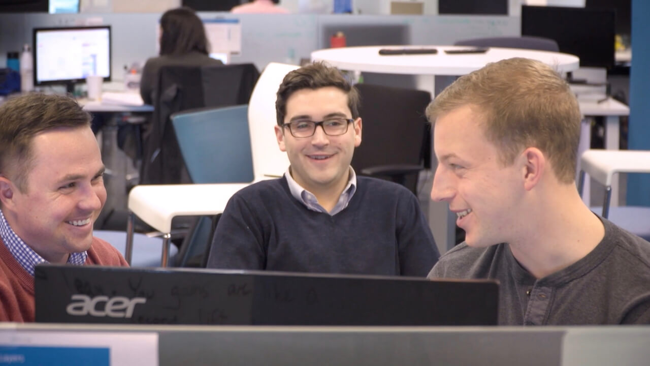 Three QA Symphony employees smile while discussing why they work at QA Symphony.
