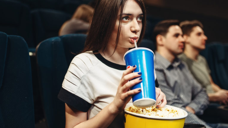 A woman with a beverage and popcorn sits in a movie theater to watch films from herspective.
