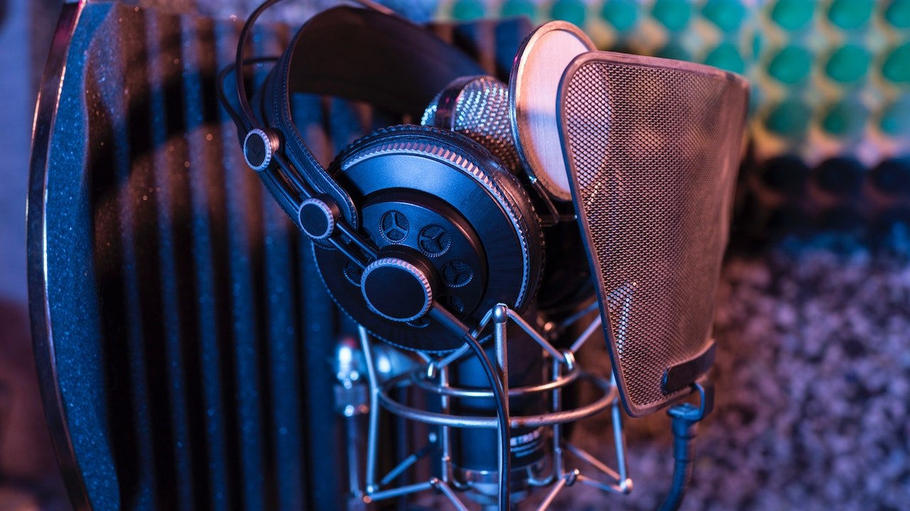 A microphone, pair of headphones, and a sound shield in a recording booth.