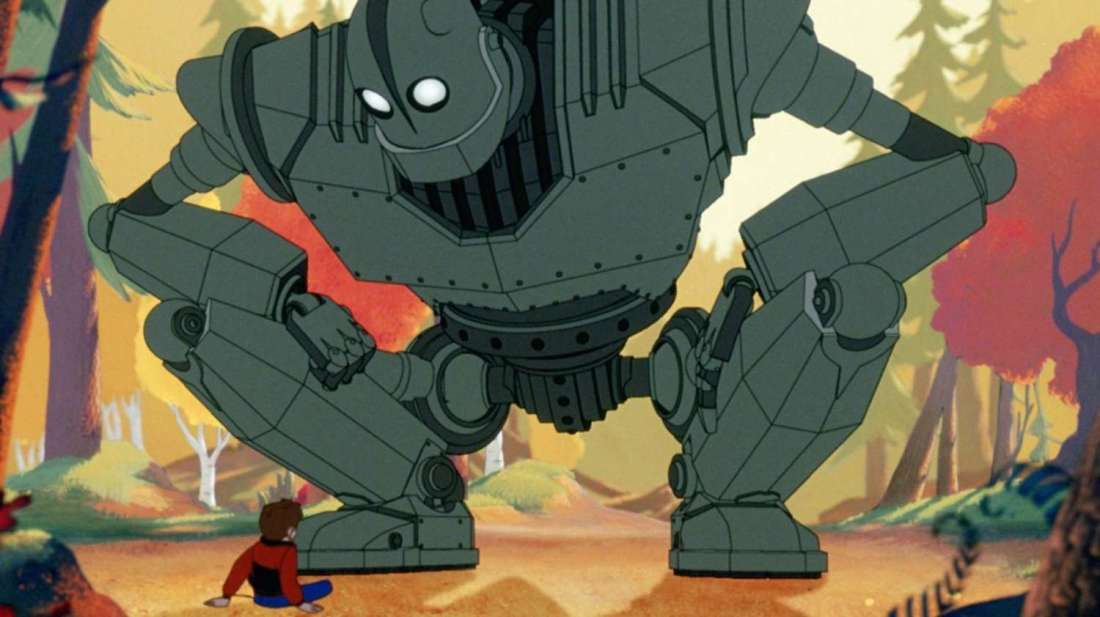 The iron giant squats down and faces a boy.