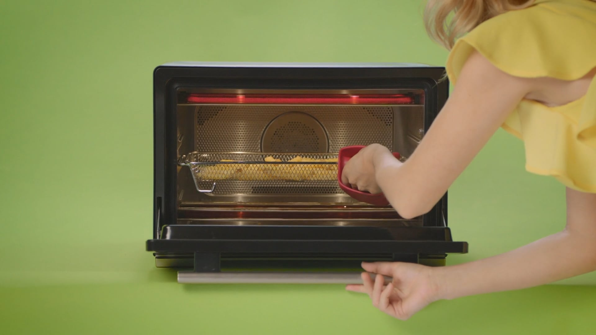 A lady reaches into a smart oven with a red oven mitt.