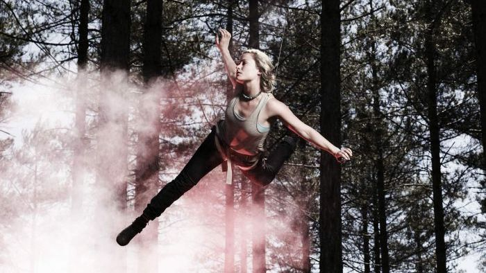 A stunt woman in an action harness mid-air in a forrest
