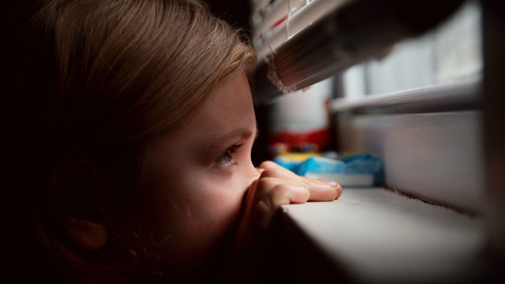 Girl looks out window during coronavirus self-quarantine