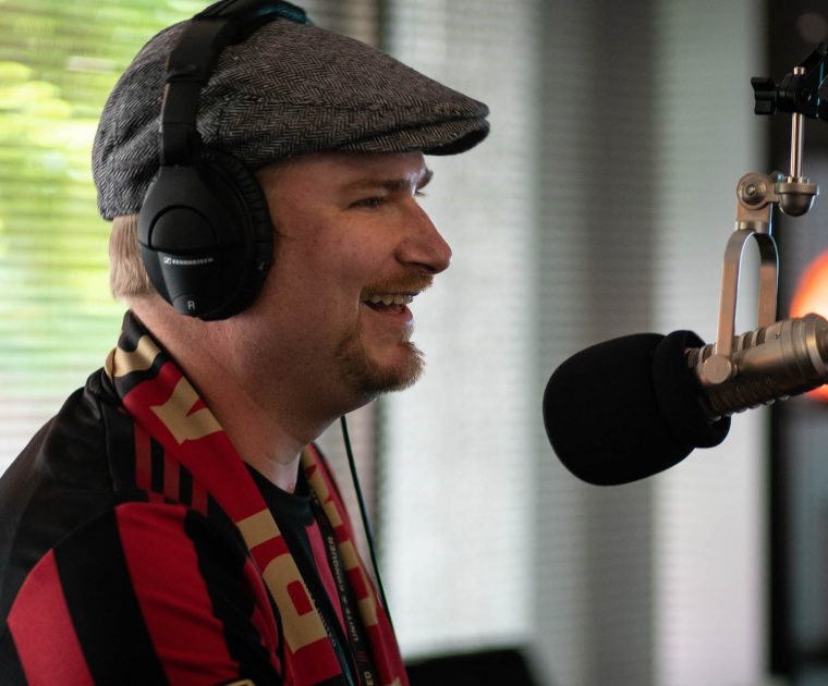 man laughs into microphone during podcast recording