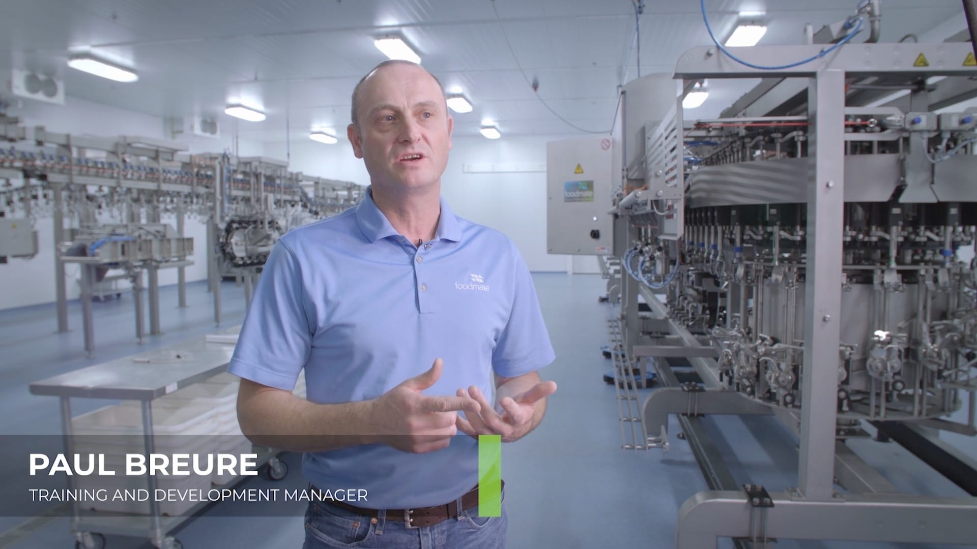 A man in a blue polo in a Foodmate production facility is filmed for a 2019 recruitment video.