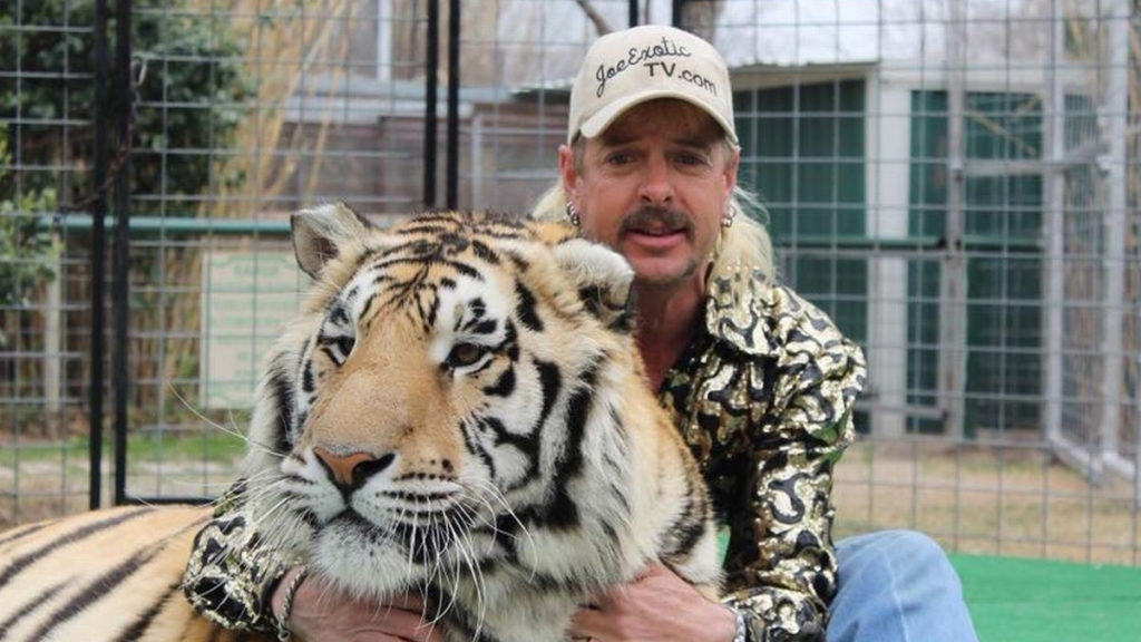 Joe Exotic, known as 'Tiger King,' poses with a tiger.
