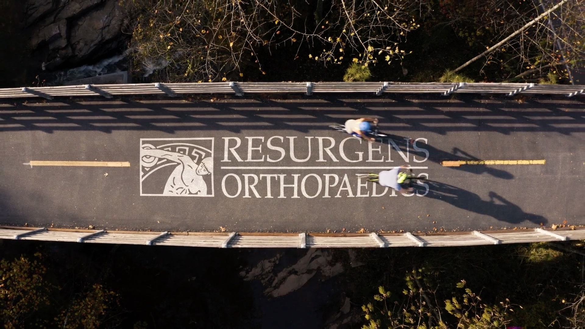 Two cyclists on the Silver Comet Trail pass over the words Resurgens Orthopaedics.
