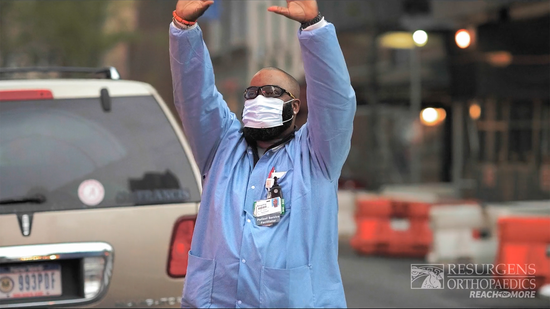 A medical professional standing in the street waves his hands as he keeps reaching.