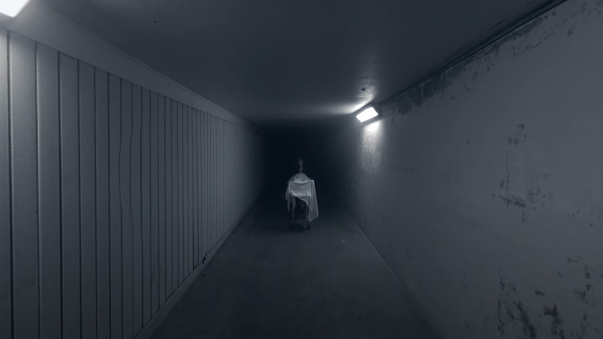 A cadaver covered by a sheet is wheeled down a dark hallway.